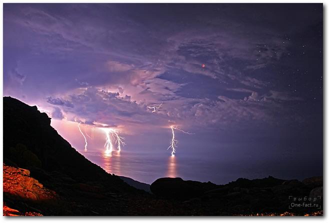 В момент полного лунного затмения началась гроза, но небо было закрыто облаками не полностью и фотографу удалось поймать фантастическое сочетание — грозовые тучи, звезды, красную Луну и молнии, бьющие в море.